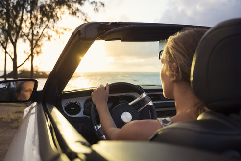 Woman in car by beach at sunset - FOLF00582