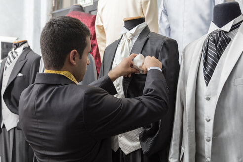 Tailor putting dress handkerchief into tuxedo in tailor shop - LFEF00106