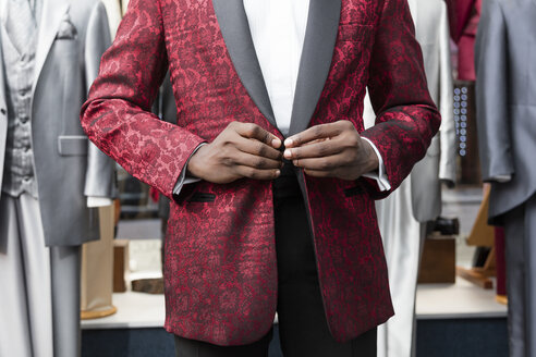 Mid section of a man dressing tuxedo in tailor shop - LFEF00109