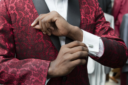 Close-up of a man wearing tuxedo in tailor shop adjusting the sleeves - LFEF00112
