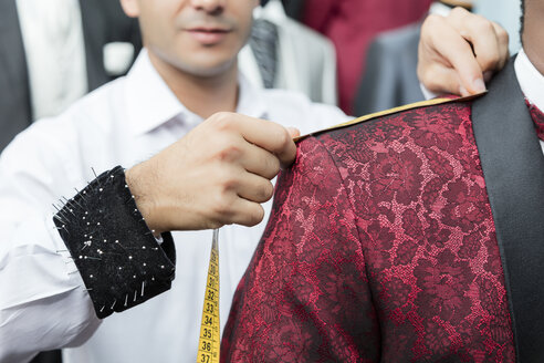 Detail of tailor measuring up client wearing tuxedo in tailor shop - LFEF00115