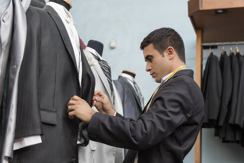 Tailor examining tuxedo in tailor shop - LFEF00118