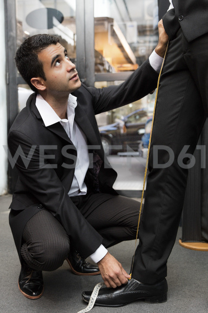 Tailor measuring up leg of a client in tailor shop - LFEF00121