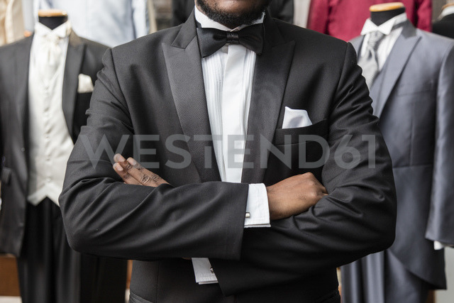 Mid section of a man with arms crossed wearing tuxedo in tailor shop - LFEF00127