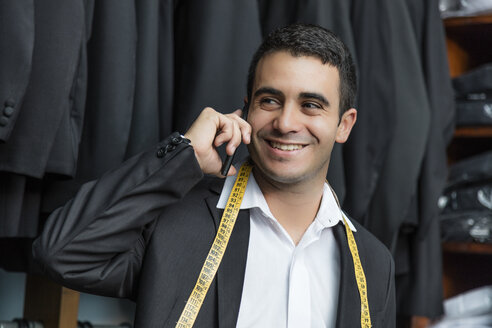 Smiling elegant tailor talking on phone in tailor shop - LFEF00130