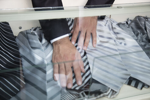 Tailor tidying up shirts and ties in glass case - LFEF00133