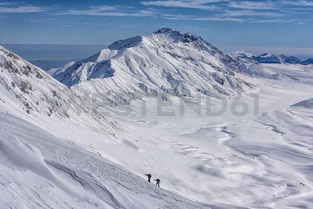Italy, Abruzzo, Gran Sasso e Monti della Laga, Hikers on Campo Imperatore plateau in winter - LOMF00711