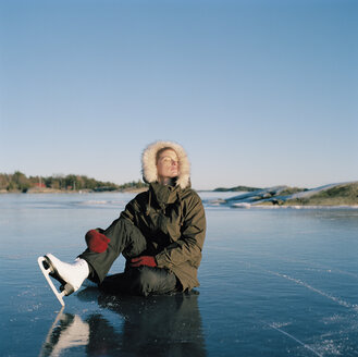 Mid adult woman sitting on frozen lake - FOLF00800