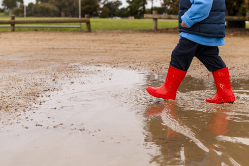 Low section of boy walking in puddle at playground - CAVF28532
