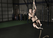 Confident athlete climbing rope at gym - CAVF28550