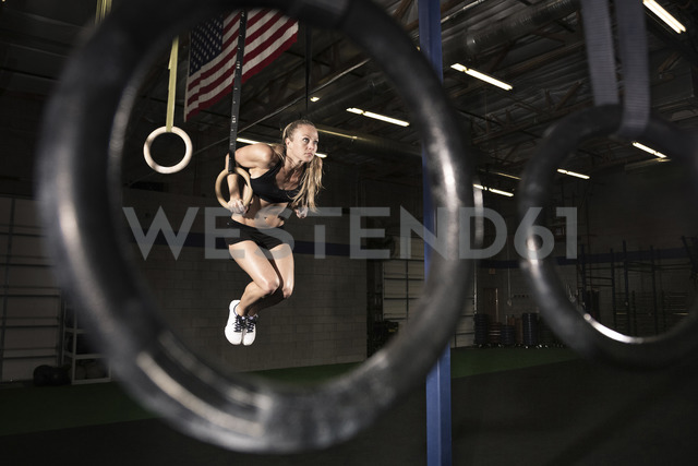 Female athlete exercising on gymnastic rings at health club - CAVF28553