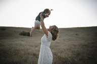 Side view of mother playing with daughter while standing on field against clear sky - CAVF28571