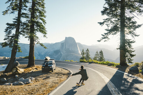 Rear view of man skateboarding on road by mountains against clear sky - CAVF28607