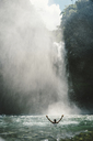 Rear view of man with arms outstretched in river by majestic waterfall - CAVF28613
