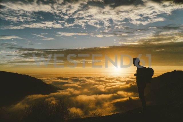 Silhouette male hiker standing on mountain during sunset - CAVF28631