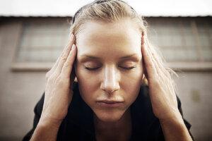 Female athlete meditating against building - CAVF28676