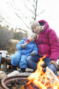 Mother with son sitting on log by campfire - FOLF01086