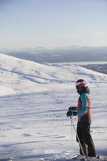 Woman in ski wear standing on mountain slope - FOLF01116