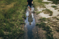 Reflection of boy holding shoes while walking in puddle - CAVF28690