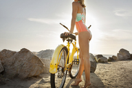 Low section of woman standing with bicycle on beach against sky - CAVF28762