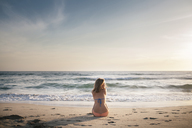 Rear view of woman sitting on beach against sky during sunset - CAVF28768