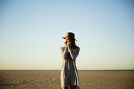 Thoughtful woman standing on beach against clear blue sky - CAVF28789