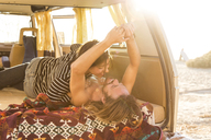 Happy romantic couple in mini van during summer vacation on San Onofre State Beach - CAVF28813