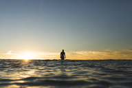 Distant view of female surfer on sea against sky during sunset - CAVF28816