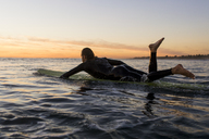Side view of man lying on surfboard in sea during sunset - CAVF28822
