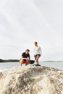 Couple doing barbeque on large rock - FOLF01273