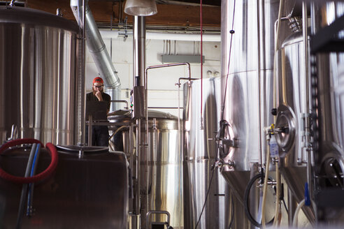 Brewer standing by storage tanks at brewery - CAVF28855