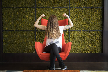 Woman with hair on face flexing muscles while sitting on armchair against wall at home - CAVF28882