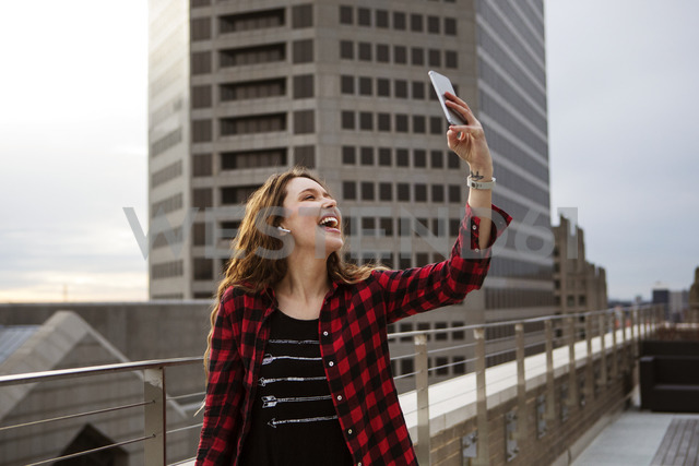 Cheerful young woman taking selfie while standing on terrace against building - CAVF28900