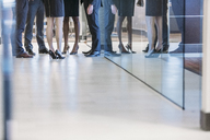 Low section of business people standing in office corridor - CAVF28939