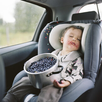 Portrait of girl sleeping in car seat with pot full of blueberries on lap - FOLF01435