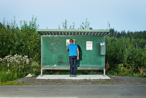 Man watching timetable at bus stop in summertime - FOLF01447