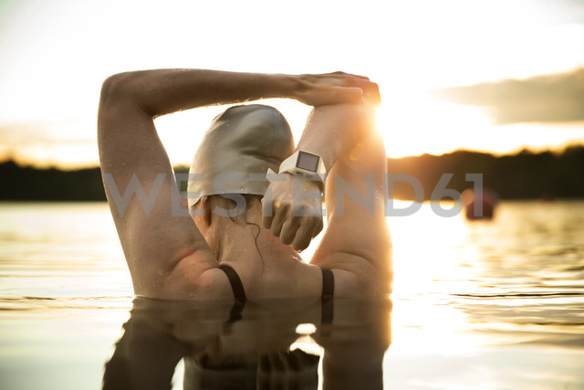 Rear view of female swimmer stretching arms in lake during sunset - CAVF29144 - Cavan Images/Westend61