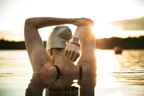 Rear view of female swimmer stretching arms in lake during sunset - CAVF29144