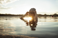 Female swimmer wearing swimming goggles in lake during sunset - CAVF29150