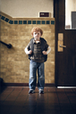 Portrait of boy carrying backpack while standing outside classroom - CAVF29192