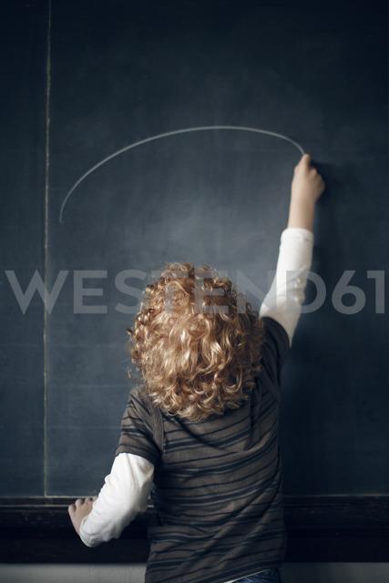 Rear view of schoolboy drawing on blackboard - CAVF29195 - Cavan Images/Westend61
