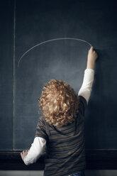 Rear view of schoolboy drawing on blackboard - CAVF29195