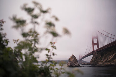 Low angle view of Golden Gate Bridge over bay against cloudy sky - CAVF29273
