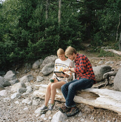 Couple using tablet pc in forest - FOLF01585