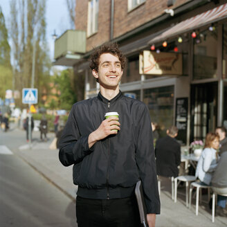 Smiling man standing on street with laptop and disposable cup in hand - FOLF01603