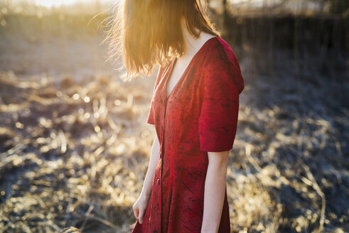 Young red hair woman in red dress standing in sunlight - FOLF01642