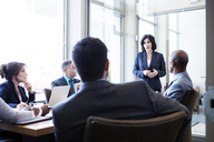 Businesswoman talking with colleagues during meeting in office - CAVF29334