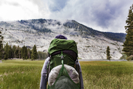 Hiker carrying backpack while looking at mountain in Yosemite National Park - CAVF29361