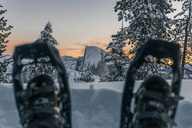 Low section of man wearing snowshoes on snowcapped mountain at Yosemite National Park during sunset - CAVF29388