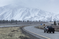 Pick-up truck on road leading towards snowcapped Mammoth Mountain - CAVF29397